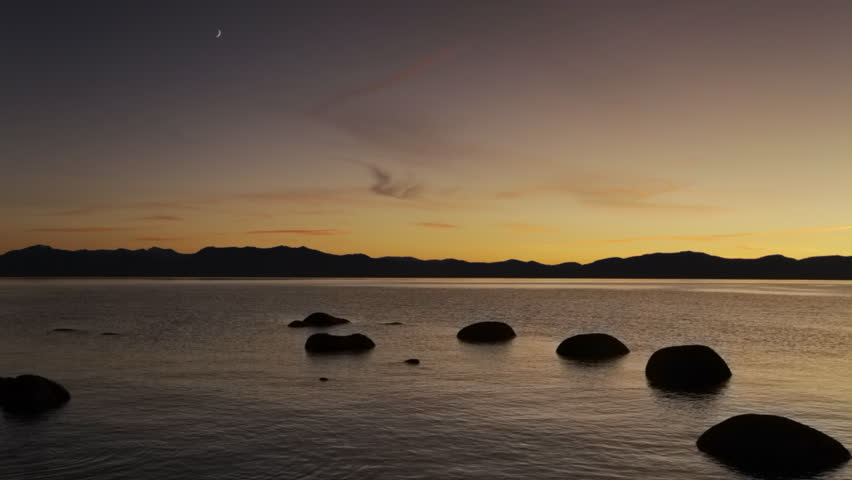 A crescent moon over Lake Tahoe at dusk, with silhouetted, boulders in the foreground and the Sierra Nevada mountains in the background.