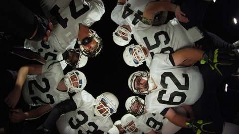 Low angle view looking up at football players inside a huddle