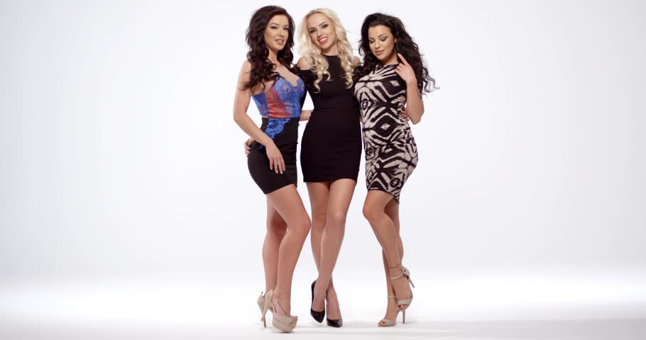 Three vivacious sexy women in sexy black miniskirt dresses and high heels  posing full length arm in arm smiling at the camera over white with  copyspace.