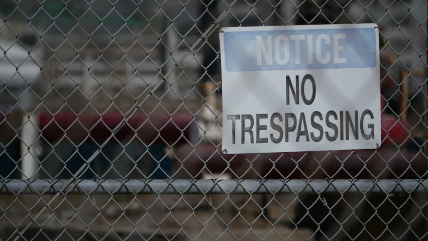 NO TRESPASSING SIGN ON A CHAIN LINK FENCE.  OLD & WEATHERED THIS SIGN WARNS OF A FORGOTTEN PAST.  LONG LENS, SOFT FOCUS BACKGROUND. SHOT IN 4K.  VERY INDUSTRIAL ESTABLISHING SHOT