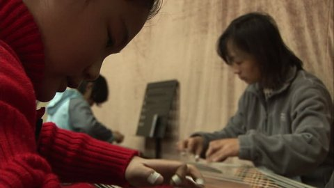 Beijing, China - February 2008: Music students strumming the guzheng zither, a traditional Chinese string instrument, with their teacher. Beijing, China.
