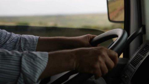 Man's hands driving a truck