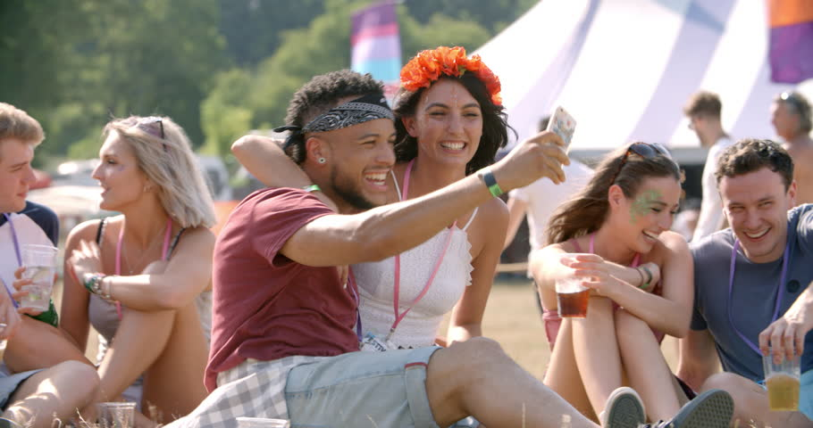 Friends sitting on grass taking selfie at a music festival | Shutterstock HD Video #12601529