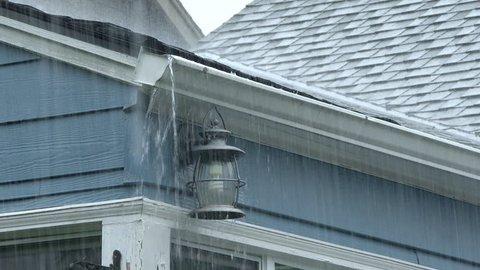 Heavy rain falling on house fills up house gutters in Portland, Oregon.