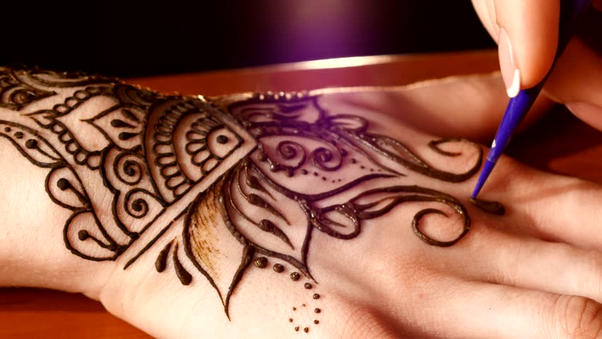 Woman hand being decorated with henna tattoo, mehendi, on black background