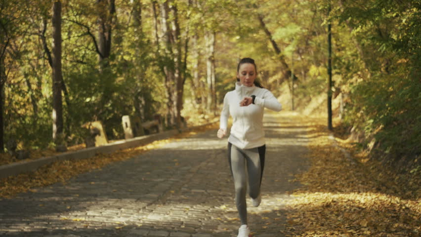 Running looking at heart rate monitor smartwatch while running. Women runner jogging outside looking at sports smart watch during workout training for marathon run. | Shutterstock HD Video #12613919