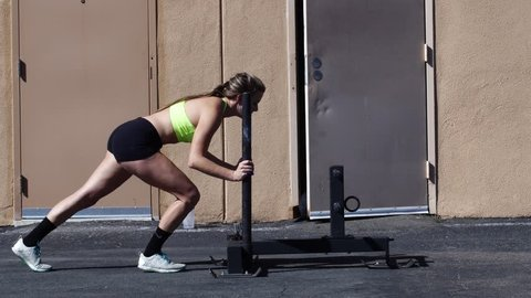 Young woman doing a sled push.