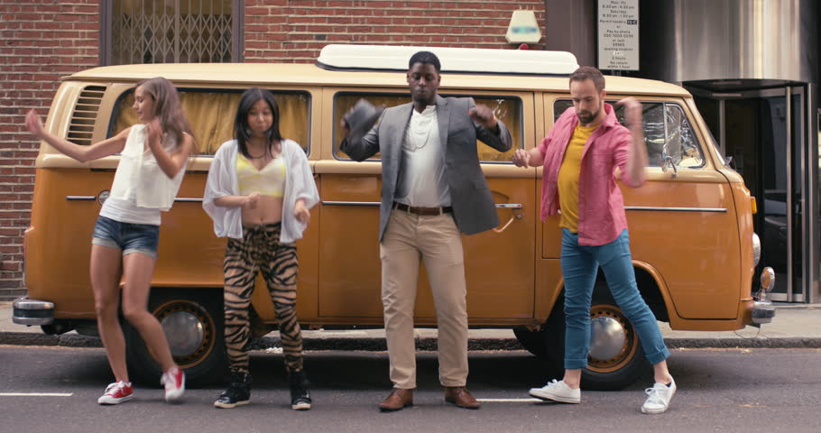 Group of multi-racial dancers street dancing vintage camper van funky freestyle in the city