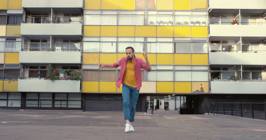 Colorful happy caucasian dancer man funky street dancing freestyle in the city