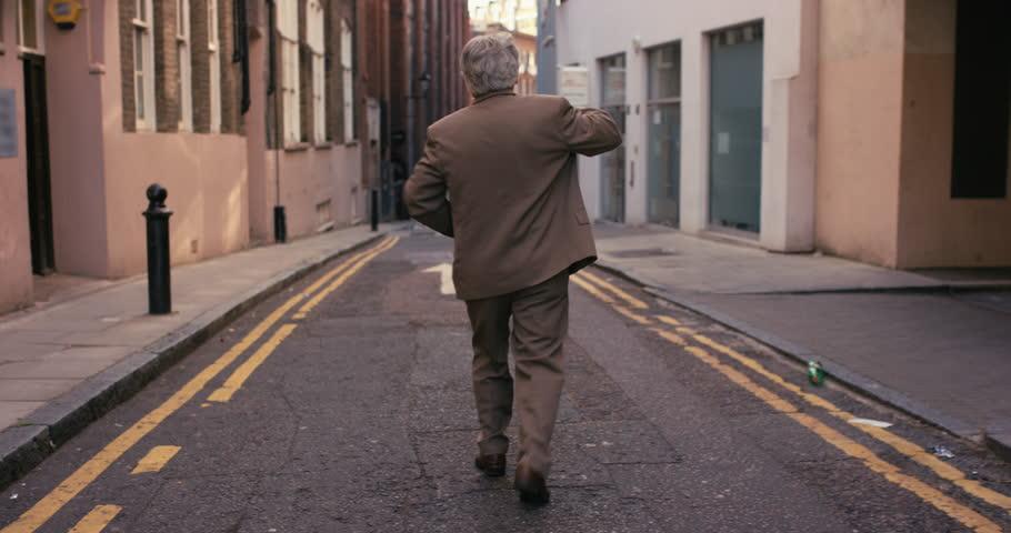 Happy elderly dancer man wearing suit funky street dancing freestyle in the city