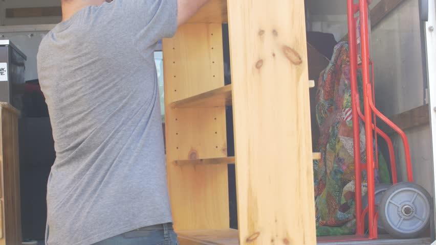 Man sets down bookshelf in moving truck