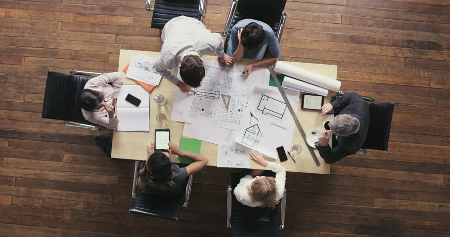 Top View of Business people meeting around boardroom table discussing architectural plans for new sustainable shared office space | Shutterstock HD Video #12702359