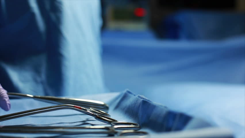 A surgical tool is handed to a surgeon in an operating room setting with out of focus blinking light in the background.