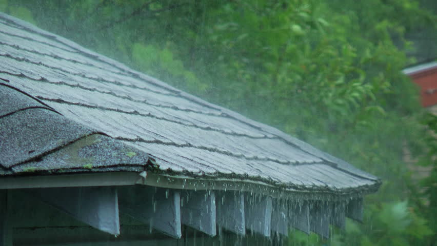 Heavy rain falling on the edge of a roof.