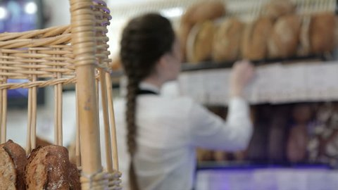 Girl baker put price labels on bread. Young smiling baker inside the coffee shop or bakery offers fresh breads, pastries, muffins, macaroon, muffins. The assortment of the new bakery, coffee shop is