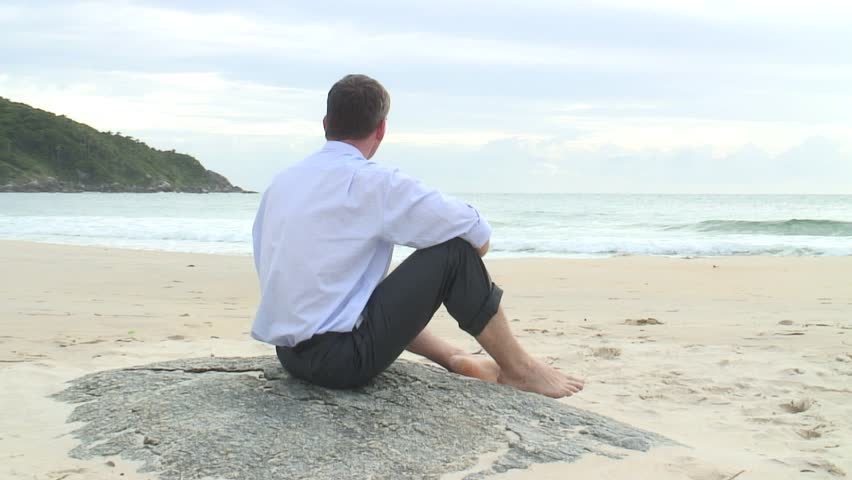 Businessman sitting on a rock on the beach watching the waves.