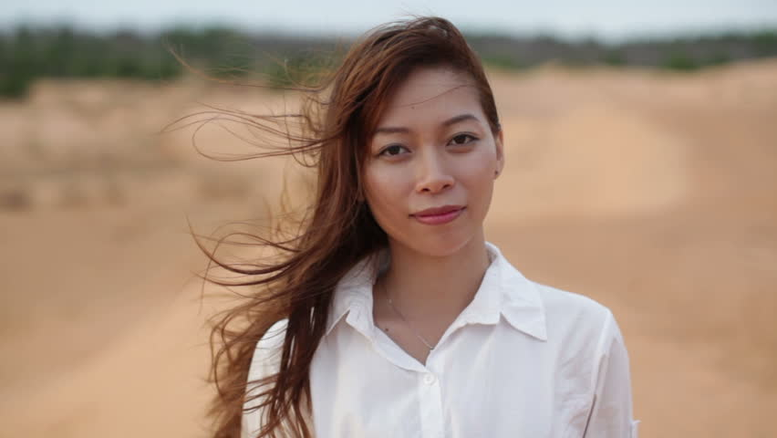 Asian woman smile outdoor desert wind blowing hair, wear white shirt close up face of young happy girl looking to camera cheerful | Shutterstock HD Video #12757997