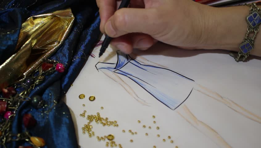 Clothing designer creates sketch by hand In Fashion Design Studio. Fashion designer create women's apparel. She sketches design, selects fabrics, embellishments, colors
