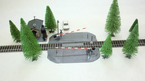 The model of the railway crossing: moving cars and trains around the trees. Stop motion.