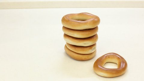 On the table there are bagels, are added to the stack, move the table and disappear. Stop motion.