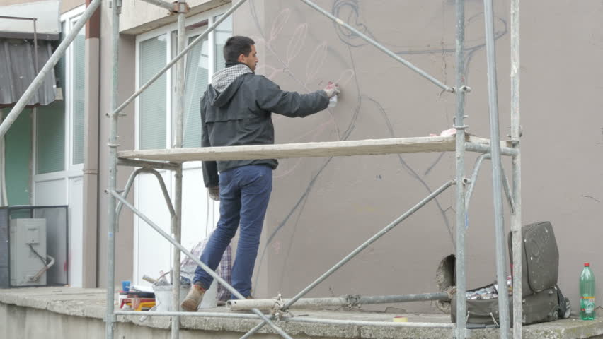 Talented Young Man Standing On Scaffold And Painting Mural Or ...