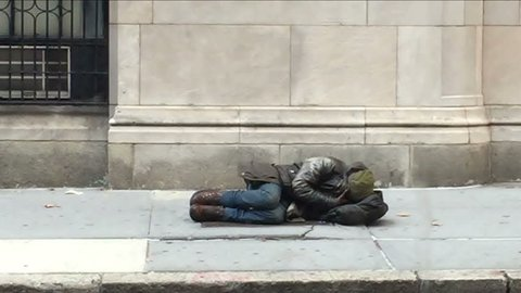 NEW YORK - NOV 13, 2015: homeless man sleeping in the street while woman on cell phone passes by in NY. Homelessness is still a major problem in New York City.