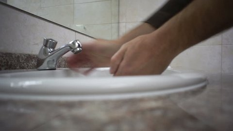 Close up shot of a man in a public washroom taking soap from the dispenser then trying to start the water tap that does not work and then moving to another to wash his hands.