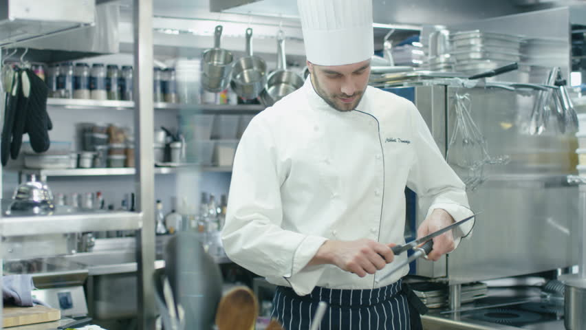 Restaurant Kitchen Video a cook sharpening a knife in a restaurant kitchen stock footage