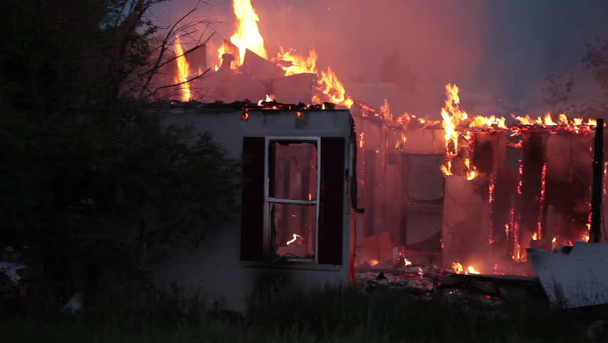 House fire during the night with flames burning the roof and walls, pan fast motion. Total destruction and lose