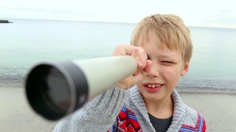 Funny little boy looking through telescope at camera at sea background. 8 years old child enjoying nature. Real time video clip.