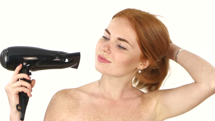 Redhead woman in bathroom drying hair with blow dryer, lovely woman in towel. white background. Close up, Black hair dryer, bathroom