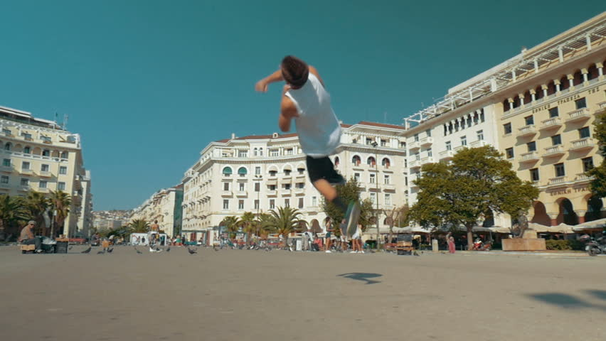 Slow motion steadicam shot of a young acrobat performing flips in the city street. Urban sportive lifestyle