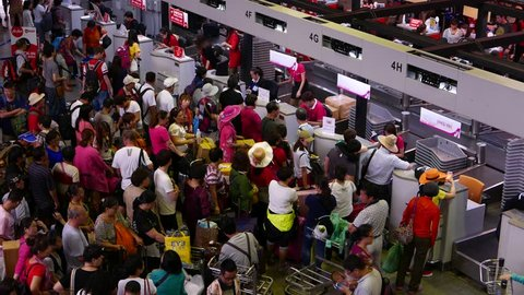 BANGKOK - MARCH 30, 2015: Overcrowded check-in counters, unidentified chinese passengers throng around, Don Mueang, DMG, old international airport. Camera located above, high angle view from top