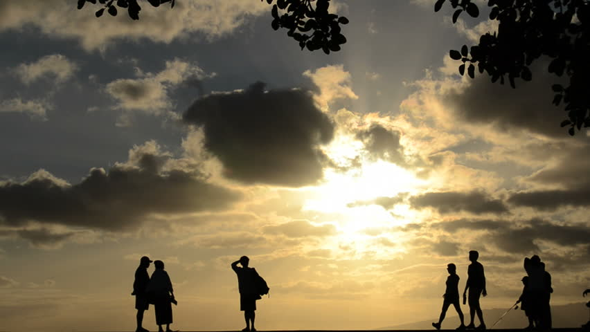 People walking, jogging, fishing at a park by the beach at sunset in Hawaii