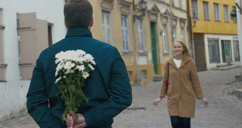 Young couple is having a date on the street of Tallinn. Man is giving a bunch of flowers to a woman.