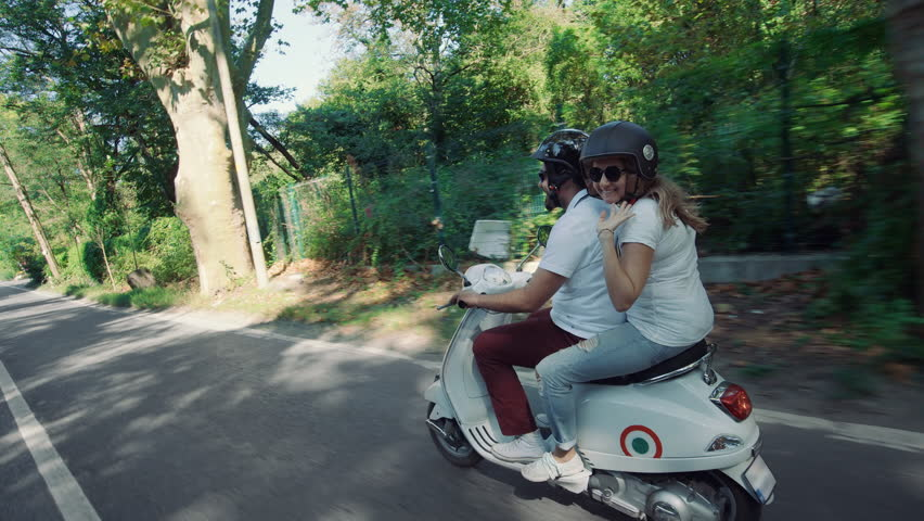 Slow motion side shot of young Caucasian couple riding their scooter through forest. Girl looks at camera and waves her hand.