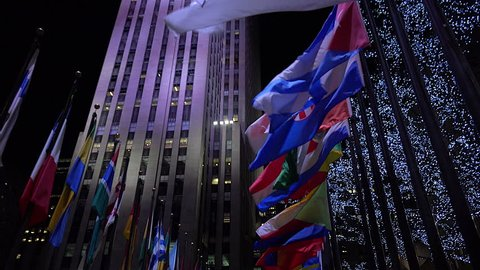 NEW YORK CITY - CIRCA 2015 - Tilt up shot to reveal Rockefeller Center in New York City at night with flags flying.