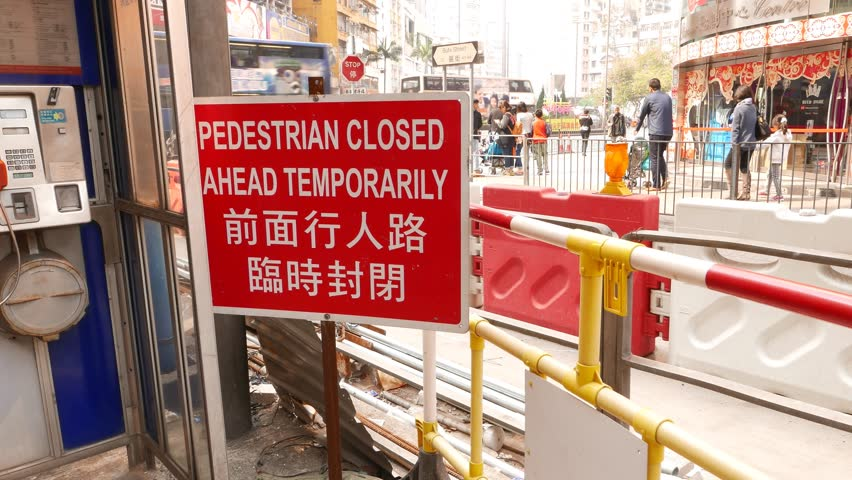 HONG KONG - FEBRUARY 09, 2015: Road reconstruction area, walk behind fence, watch red sign message. Day city life on back. Compact area full of alerts, fence parts, sign boards. Excavated road behind
