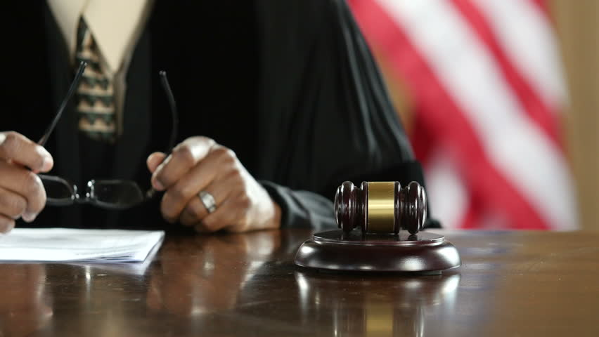 Judge's hand banging a gavel in a courtroom