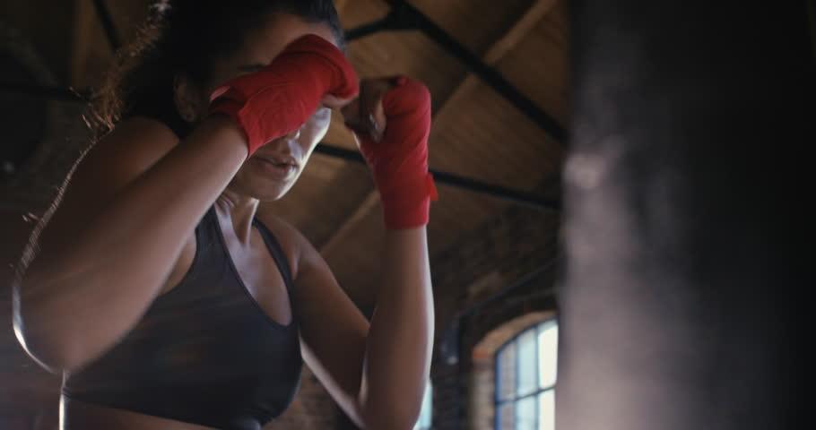 Beautiful Kickboxing woman training punching bag in fitness studio fierce strength fit body kickboxer series   Shutterstock HD Video #12950321