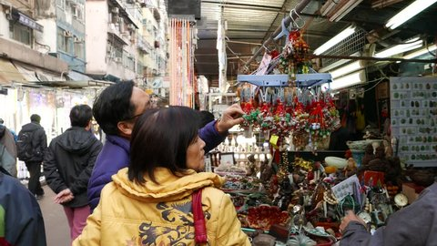 HONG KONG - FEBRUARY 09, 2015: Open street market at inner-city area. Man and woman looking up at hanging talismans, choosing which one to buy