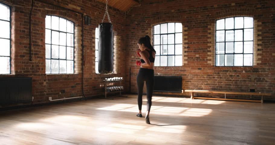 Beautiful Beautiful Kickboxing Woman Training Punching Bag In Fitness Studio Fierce  Strength Fit Body   4K Stock