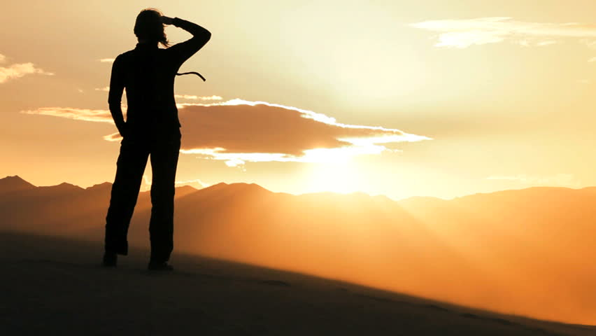 Lone female at sunset celebrates achieving her desert hike through sand dunes