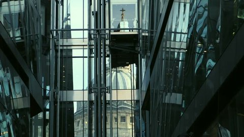 St Paul's Cathedral reflected in glass building in London. Elevator crosses the frame.