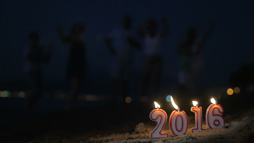 Slow motion clip of lit 2016 candles on the sand, blurred family celebrating the holiday at the seaside in background. New Year and Christmas time | Shutterstock HD Video #12967316