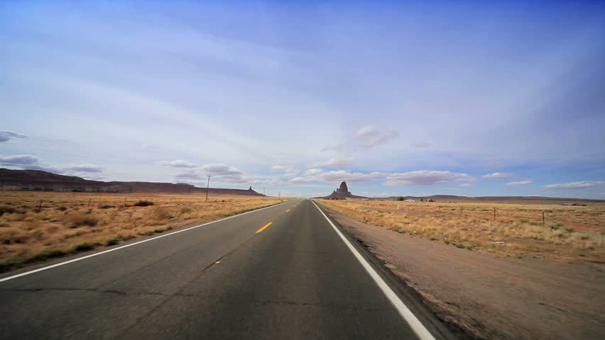 Driving the long straight road through the desert to Monument Valley, Arizona