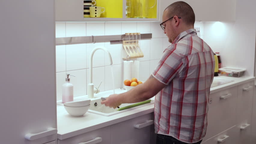 Superb The Man In The Kitchen Washing Dishes In The Sink Cleaning Brush   HD Stock  Video
