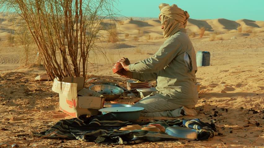 a sahara man washing dishes