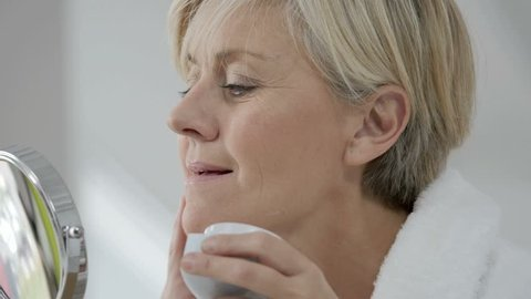 Senior woman in bathroom applying anti-aging cream