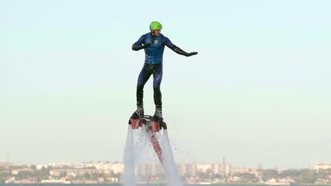 Man flying over the lake on flyboard and diving into the water